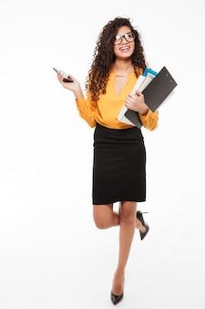 Heureux jeune femme d'affaires africaine marchant avec dossiers et téléphone portable