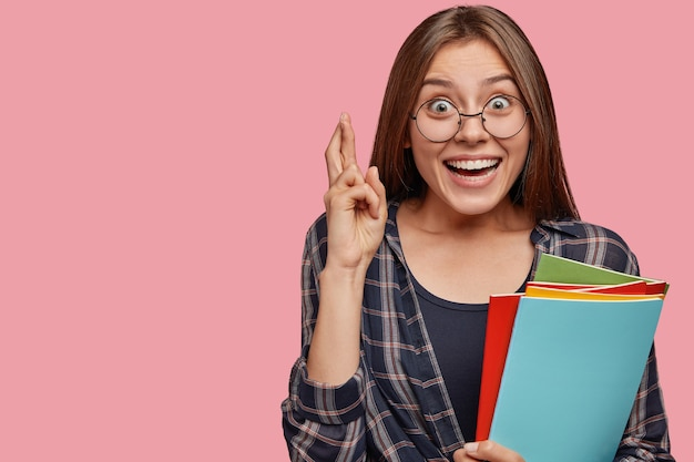 Heureux jeune femme d'affaires posant contre le mur rose avec des lunettes