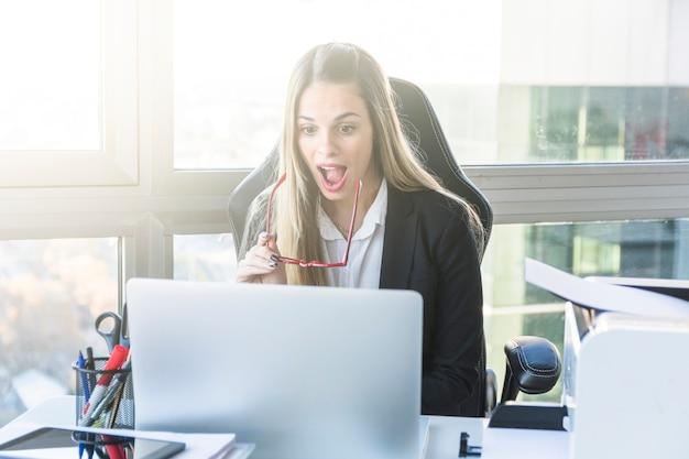 Heureux jeune femme d'affaires en regardant une tablette numérique