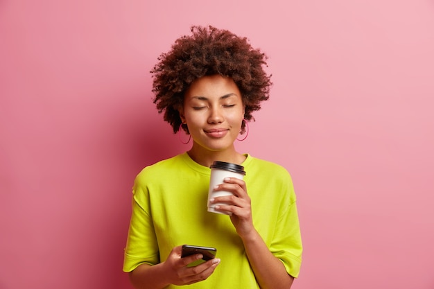 Heureux jeune femme afro-américaine bouclée ferme les yeux de l'odeur agréable de l'arôme de café a un visage détendu utilise un smartphone pour discuter en ligne dans des vêtements décontractés isolé sur un mur rose