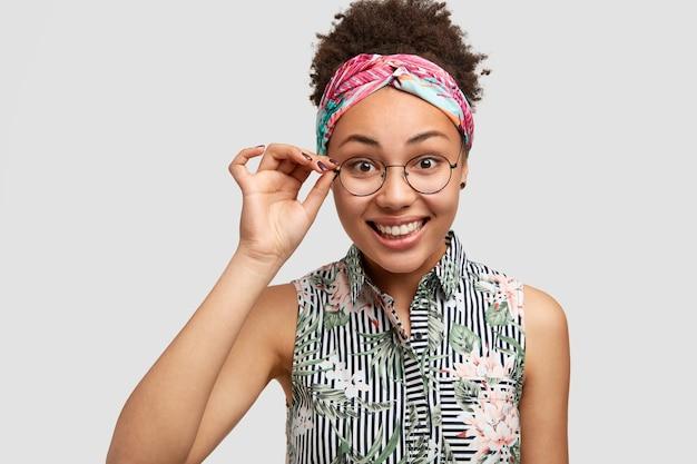 Heureux jeune femme afro-américaine à lunettes, sourit doucement