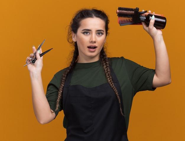 Heureux jeune femme barbier en uniforme levant des outils de barbier isolés sur un mur orange