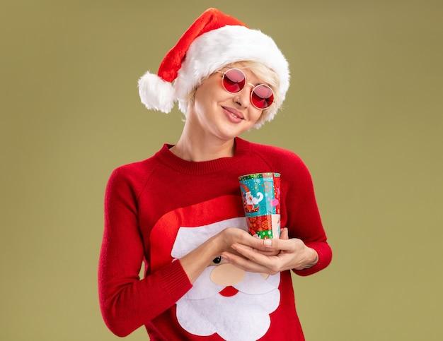 Heureux jeune femme blonde portant chapeau de noël et pull de noël du père noël avec des lunettes tenant une tasse de noël en plastique avec les yeux fermés isolé sur fond vert olive avec espace copie