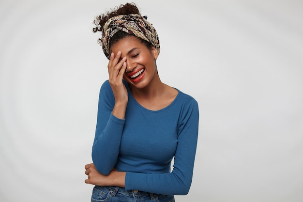 Heureux jeune femme brune frisée attrayante levant la main sur son visage et souriant joyeusement avec les yeux fermés en se tenant debout sur fond blanc