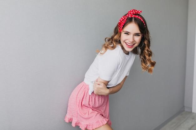Heureux jeune femme avec une coiffure frisée debout près du mur de lumière. heureux modèle féminin porte un ruban rouge dans les cheveux souriant