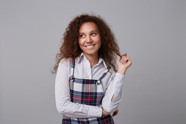 Heureux jeune femme frisée aux cheveux longs mordant sa lèvre inférieure tout en regardant positivement vers le haut et en jouant avec ses cheveux, isolé sur fond gris