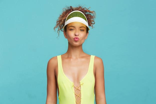 Heureux jeune femme frisée rousse attrayante faisant la moue ses lèvres et plissant les yeux tout en regardant la caméra, isolée sur fond bleu avec les mains vers le bas