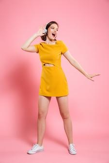 Heureux jeune femme heureuse en robe jaune danse