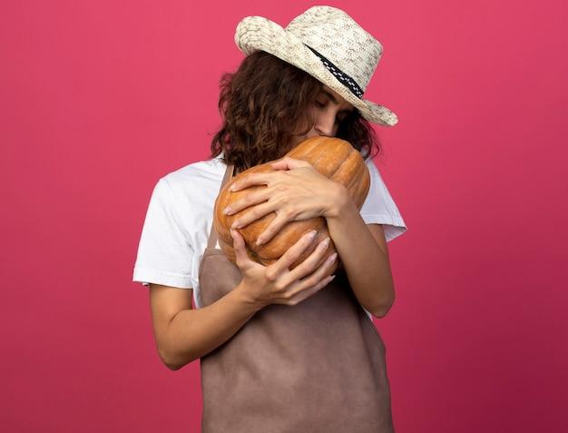 Heureux jeune femme jardinier en uniforme portant chapeau de jardinage tenant et embrassant la citrouille isolé sur rose