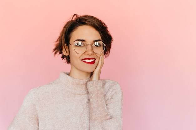 Heureux jeune femme à lunettes touchant le visage
