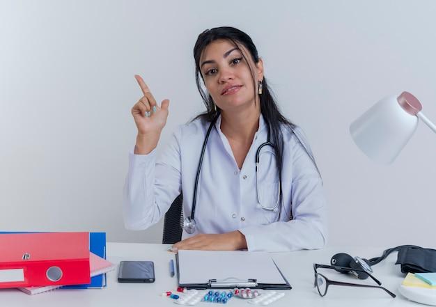 Heureux jeune femme médecin portant une robe médicale et un stéthoscope assis au bureau avec des outils médicaux à mettre la main sur le bureau en levant le doigt isolé