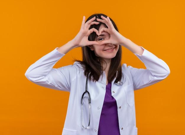 Heureux jeune femme médecin en robe médicale avec stéthoscope regarde par-dessus le geste du cœur sur fond orange isolé