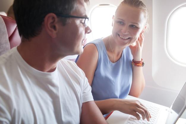 Heureux jeune et femme avec un ordinateur portable dans l'avion