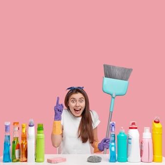 Heureux jeune femme avec des points d'expression heureux ci-dessus, montre un espace de copie pour votre contenu publicitaire, porte une brosse ou un balai