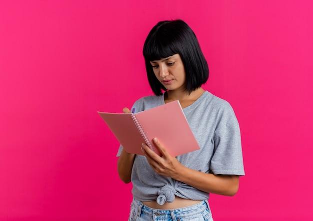 Heureux jeune femme de race blanche brune écrit avec un stylo dans un cahier isolé sur fond rose avec copie espace