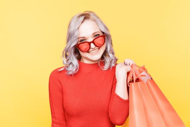 Heureux jeune femme en robe rouge et lunettes de soleil debout avec des sacs dans la chambre jaune.