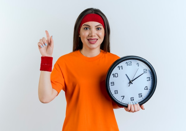 Heureux jeune femme sportive portant bandeau et bracelets tenant horloge regardant vers le haut