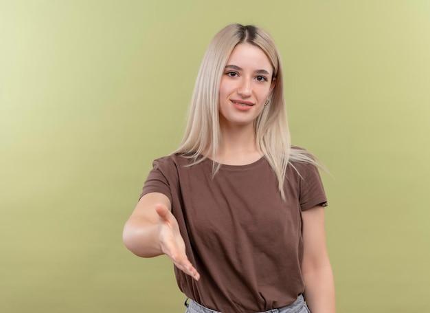 Heureux jeune fille blonde dans un appareil dentaire qui s'étend de la main faisant des gestes salut sur un espace vert isolé avec copie espace