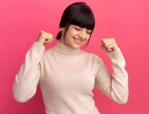 Heureux jeune fille brune caucasienne garde les poings levés