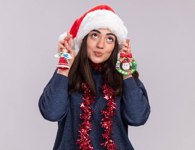 Heureux jeune fille caucasienne avec bonnet de noel et guirlande autour du cou tient des jouets d'arbre de noël en levant isolé sur mur blanc avec espace de copie