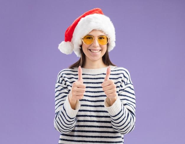 Heureux jeune fille caucasienne à lunettes de soleil avec chapeau de père noël pouces vers le haut