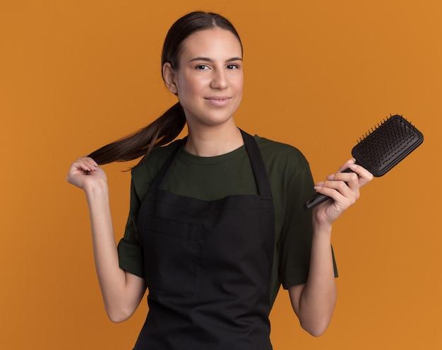 Heureux jeune fille de coiffeur brune en uniforme détient tresse et peigne sur orange