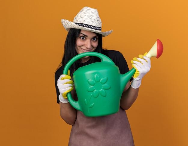 Heureux jeune fille de jardinier de race blanche en uniforme et chapeau avec des gants de jardinier tenant un arrosoir