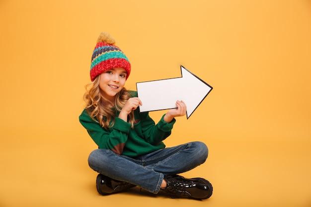 Heureux jeune fille en pull et chapeau assis sur le sol tout en pointant avec la flèche de papier loin et en regardant la caméra sur orange