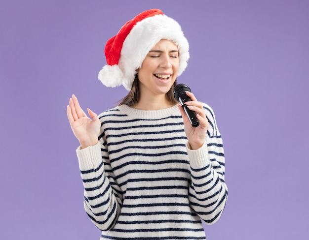 Heureux jeune fille de race blanche avec bonnet de noel détient micro faisant semblant de chanter isolé sur fond violet avec espace copie