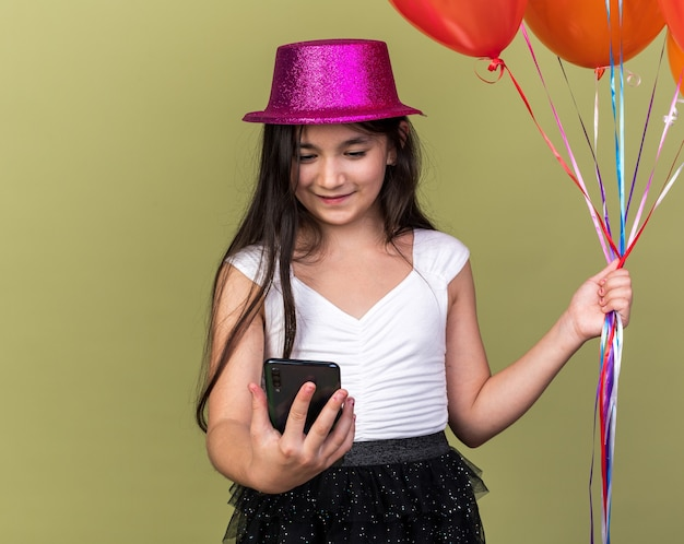 Heureux jeune fille de race blanche avec chapeau de fête violet regardant téléphone et tenant des ballons d'hélium isolés sur mur vert olive avec espace copie