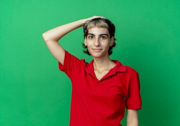 Heureux jeune fille de race blanche avec coupe de cheveux de lutin mettant la main sur la tête isolé sur fond vert avec espace de copie