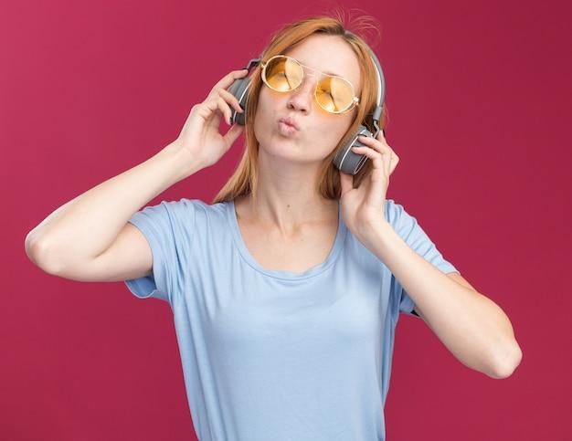 Heureux jeune fille rousse au gingembre avec des taches de rousseur dans des lunettes de soleil et sur un casque debout avec les yeux fermés sur rose
