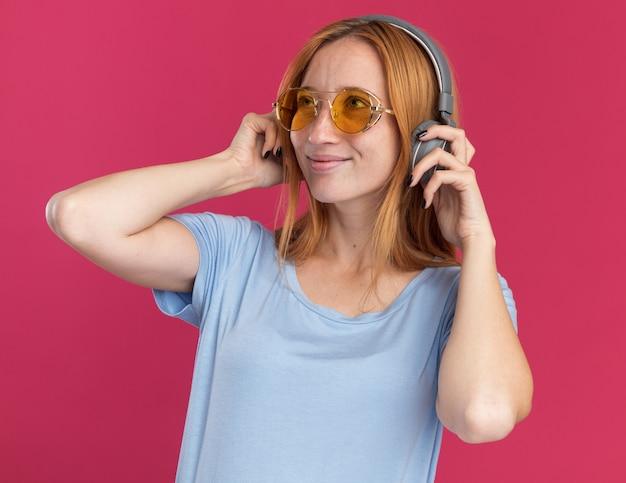 Heureux jeune fille rousse au gingembre avec des taches de rousseur dans des lunettes de soleil et sur des écouteurs à côté sur rose