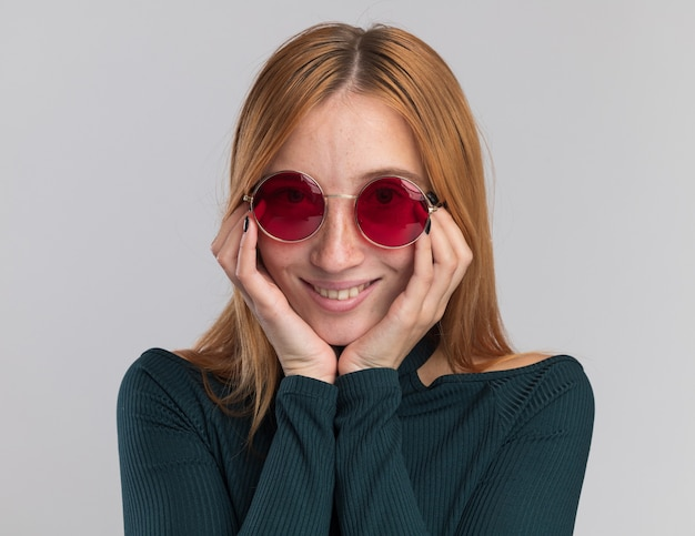 Heureux jeune fille rousse au gingembre avec des taches de rousseur dans des lunettes de soleil met les mains sur le menton sur blanc