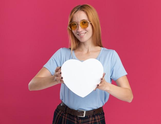 Heureux jeune fille rousse au gingembre avec des taches de rousseur dans des lunettes de soleil tient en forme de coeur sur rose