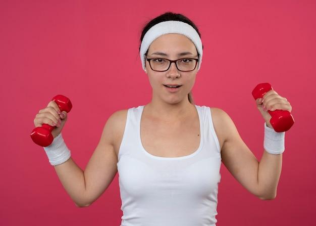 Heureux jeune fille sportive dans des lunettes optiques portant un bandeau et des bracelets tenant des haltères