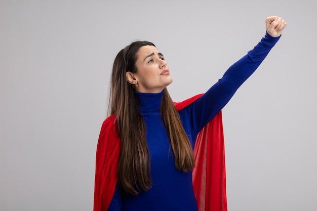 Heureux jeune fille de super-héros regardant côté levant le poing isolé sur blanc
