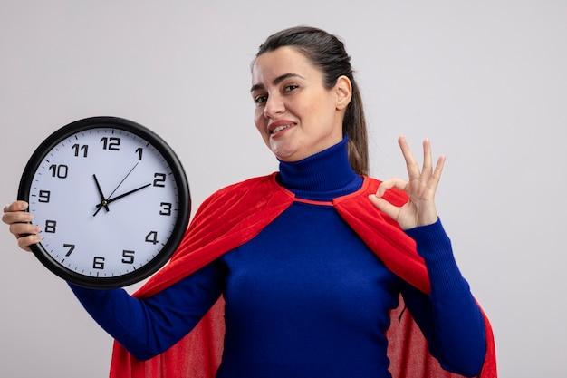 Heureux jeune fille de super-héros tenant une horloge murale et montrant le geste correct isolé sur blanc