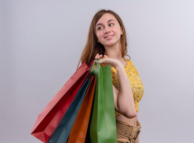 Heureux jeune fille tenant des sacs en papier sur l'épaule en regardant le côté gauche