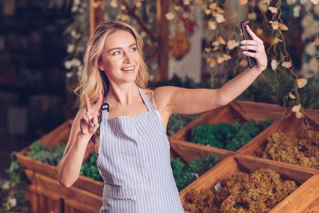 Heureux jeune fleuriste prenant selfie sur téléphone intelligent montrant le geste de la paix dans la boutique