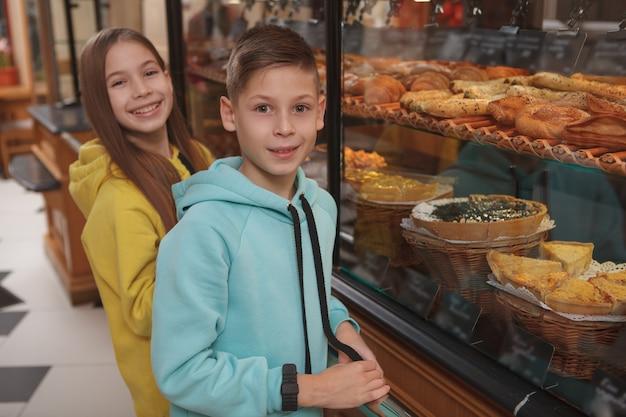 Heureux jeune frère et sœur jumeau souriant et achetant de délicieuses pâtisseries à la boulangerie locale,