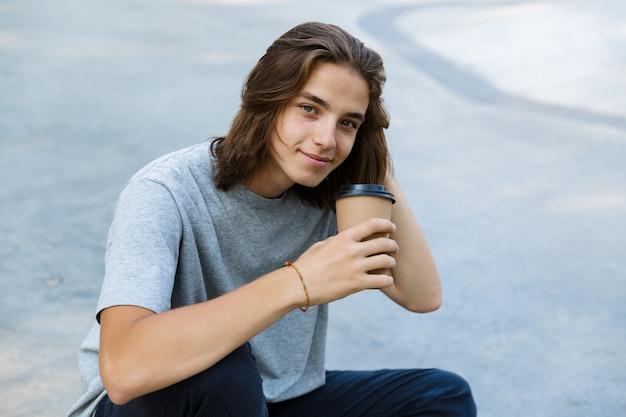 Heureux jeune garçon adolescent passer du temps au skate park, assis sur une planche à roulettes, tenant un café à emporter