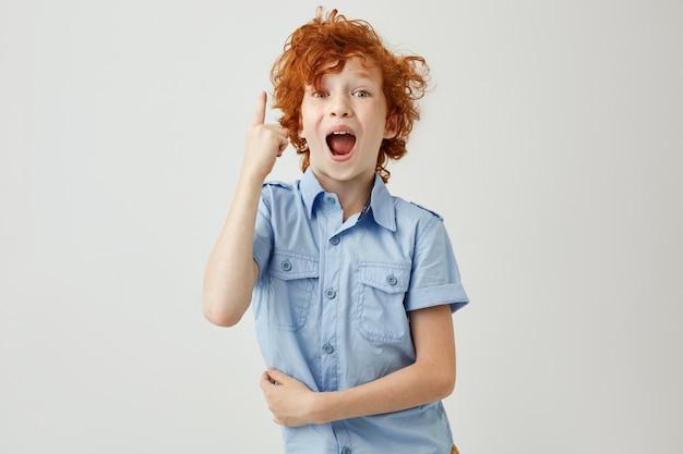 Heureux jeune garçon aux cheveux roux bouclés et taches de rousseur en chemise bleue pointant à l'envers avec une expression heureuse et excitée