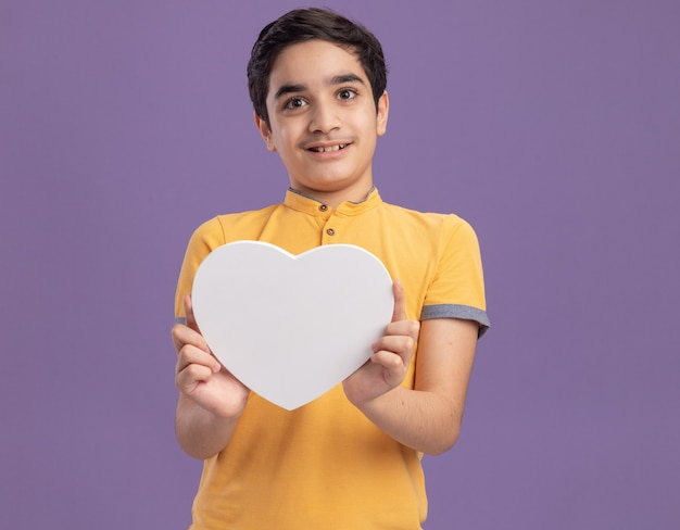Heureux jeune garçon caucasien tenant en forme de coeur