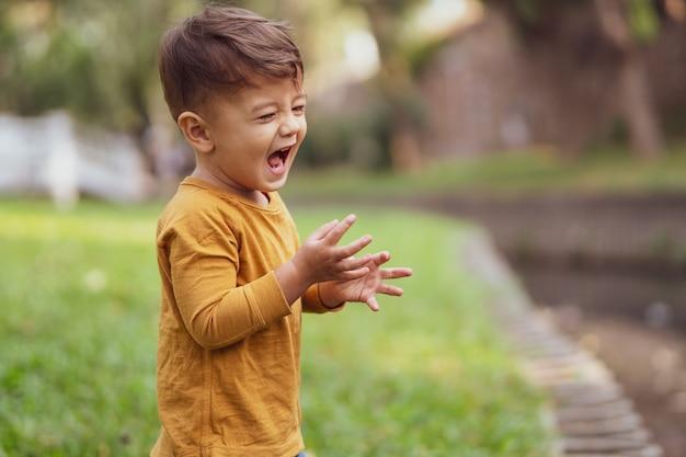 Heureux jeune garçon jouant à l'extérieur dans le parc