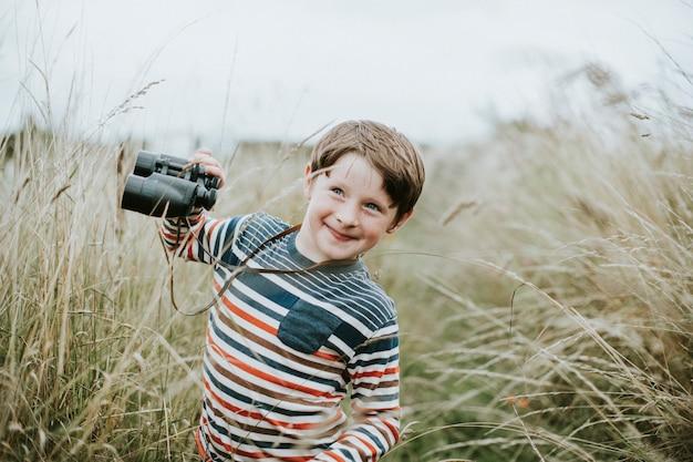 Heureux jeune garçon avec une paire de jumelles
