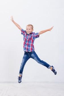 Heureux jeune garçon sautant sur blanc