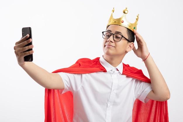 Heureux jeune garçon de super-héros en cape rouge portant des lunettes et couronne touchant la couronne prenant selfie isolé sur fond blanc