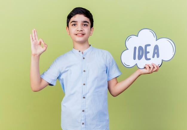 Heureux jeune garçon tenant une bulle d'idée à l'avant faisant signe ok isolé sur mur vert olive