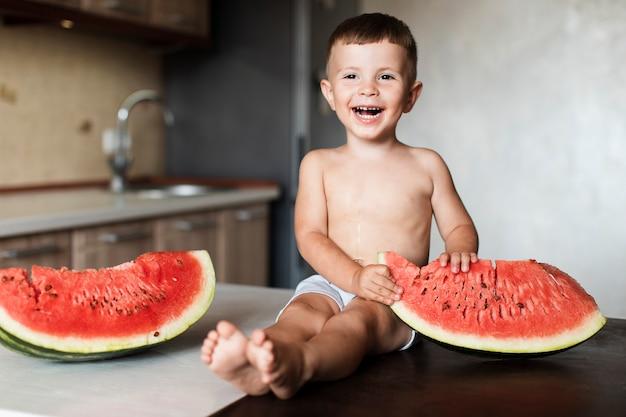 Heureux jeune garçon avec des tranches de melon d'eau
